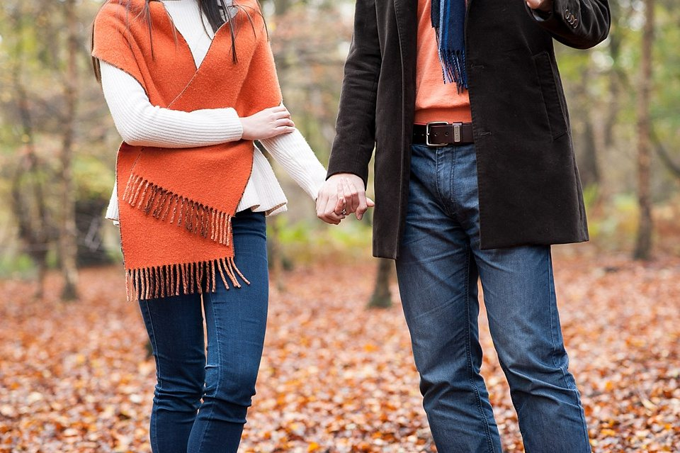 Oranges blues and browns - holding hands - Couple love shoot - Autumn engagement shoot - Epping Forest in London, Essex in England © Fiona Kelly wedding photographer