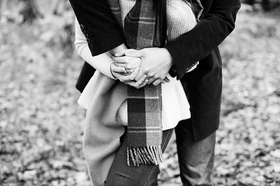 his arms around her showing engagement ring - Couple love shoot - Autumn engagement shoot - Epping Forest in London, Essex in England © Fiona Kelly wedding photographer
