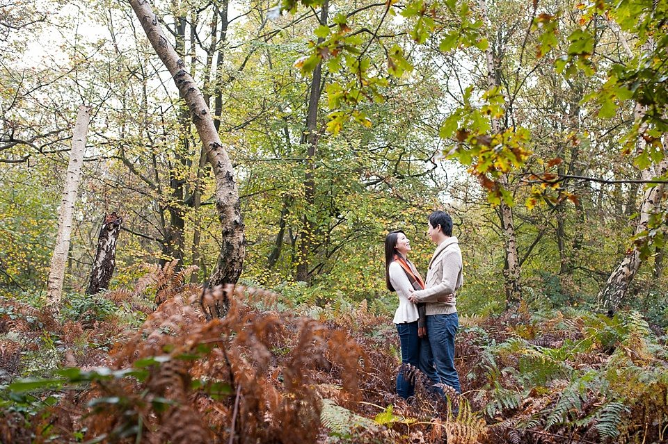 couple standing together in ferns - Couple love shoot - Autumn engagement shoot - Epping Forest in London, Essex in England © Fiona Kelly wedding photographer