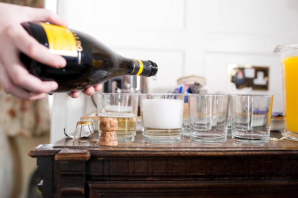 Pouring the champagne at Spread Eagle hotel - wedding accommodation for english country garden wedding Sussex wedding photographer © Fiona Kelly photography