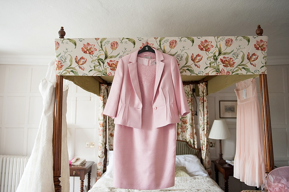 pink mother of the bride suit hanging from four poster bed - English country garden wedding at the Walled Garden at Cowdray - Sussex wedding photographer © Fiona Kelly photography