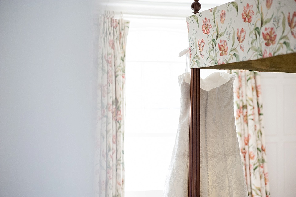 Lillian West lace wedding dress hanging from four poster bed - English country garden wedding at the Walled Garden at Cowdray - Sussex wedding photographer © Fiona Kelly photography