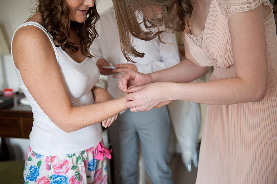 Bridesmaid in pink helping bride get ready - English country garden wedding at the Walled Garden at Cowdray - Sussex wedding photographer © Fiona Kelly photography