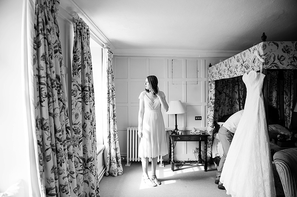 Bridesmaid looking out of the window with Lillian West wedding dress hanging - English country garden wedding at the Walled Garden at Cowdray - Sussex wedding photographer © Fiona Kelly photography
