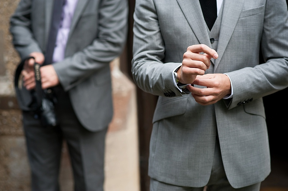 Groom adjust cuffs in grey suit - English country garden wedding All Hallows Church Woolbeding Sussex wedding photographer © Fiona Kelly photography