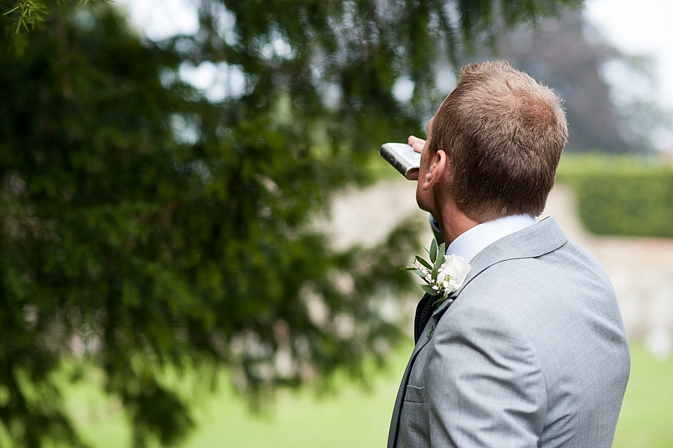 Groom in pale grey suit drinking from hip flask - English country garden wedding All Hallows Church Woolbeding Sussex wedding photographer © Fiona Kelly photography