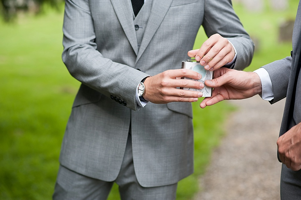 Groom and best man drinking from hip flask - English country garden wedding All Hallows Church Woolbeding Sussex wedding photographer © Fiona Kelly photography