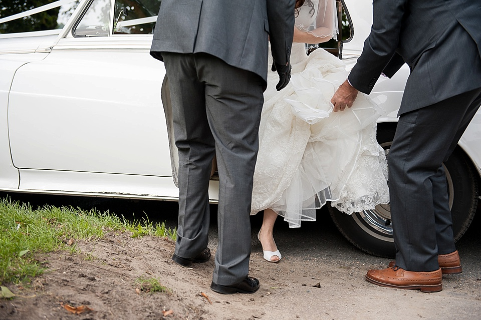 Bride getting out of vintage white car - English country garden wedding All Hallows Church Woolbeding Sussex wedding photographer © Fiona Kelly photography