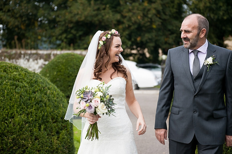 Bride with flower crown and bouquet by Blooms in Lillian West dress - English country garden wedding All Hallows Church Woolbeding Sussex wedding photographer © Fiona Kelly photography