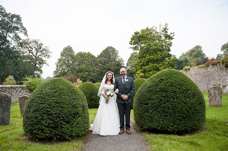 Bride wearing lace Lillian West dress standing with father - English country garden wedding All Hallows Church Woolbeding Sussex wedding photographer © Fiona Kelly photography