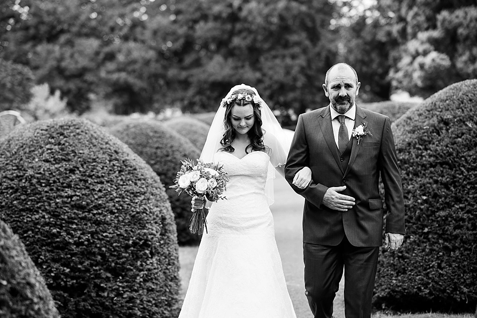 Bride in lace Lillian West dress walking with father - English country garden wedding All Hallows Church Woolbeding Sussex wedding photographer © Fiona Kelly photography