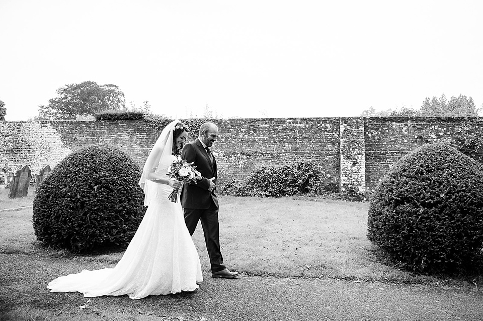 Bride walking with father in Lillian West wedding dress in black and white - English country garden wedding All Hallows Church Woolbeding Sussex wedding photographer © Fiona Kelly photography