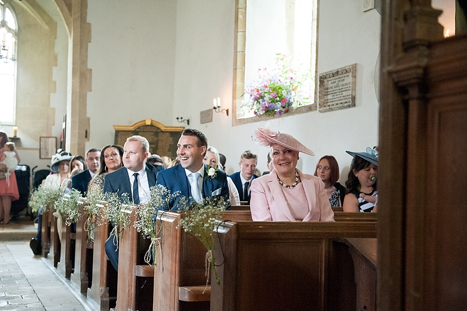 Wedding guests waiting in village church decorated with gysophilia - English country garden wedding All Hallows Church Woolbeding Sussex wedding photographer © Fiona Kelly photography
