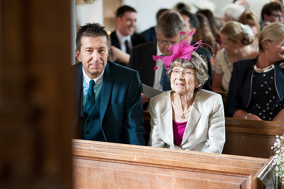 Colourful wedding guests waiting in church - English country garden wedding All Hallows Church Woolbeding Sussex wedding photographer © Fiona Kelly photography