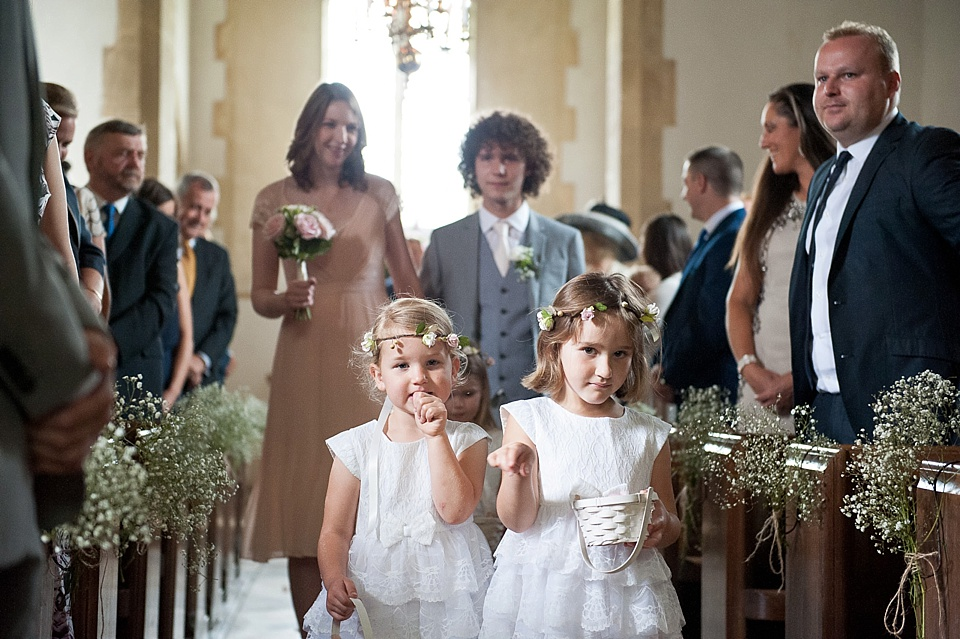 Flowergirls, bridesman and bridesmaid walk down the aisle - English country garden wedding All Hallows Church Woolbeding Sussex wedding photographer © Fiona Kelly photography