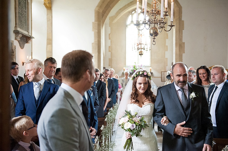 Natural bride with real flower crown and bouquet by Blooms wearing Lillian West lace wedding dress walks with father down the aisle - English country garden wedding All Hallows Church Woolbeding Sussex wedding photographer © Fiona Kelly photography