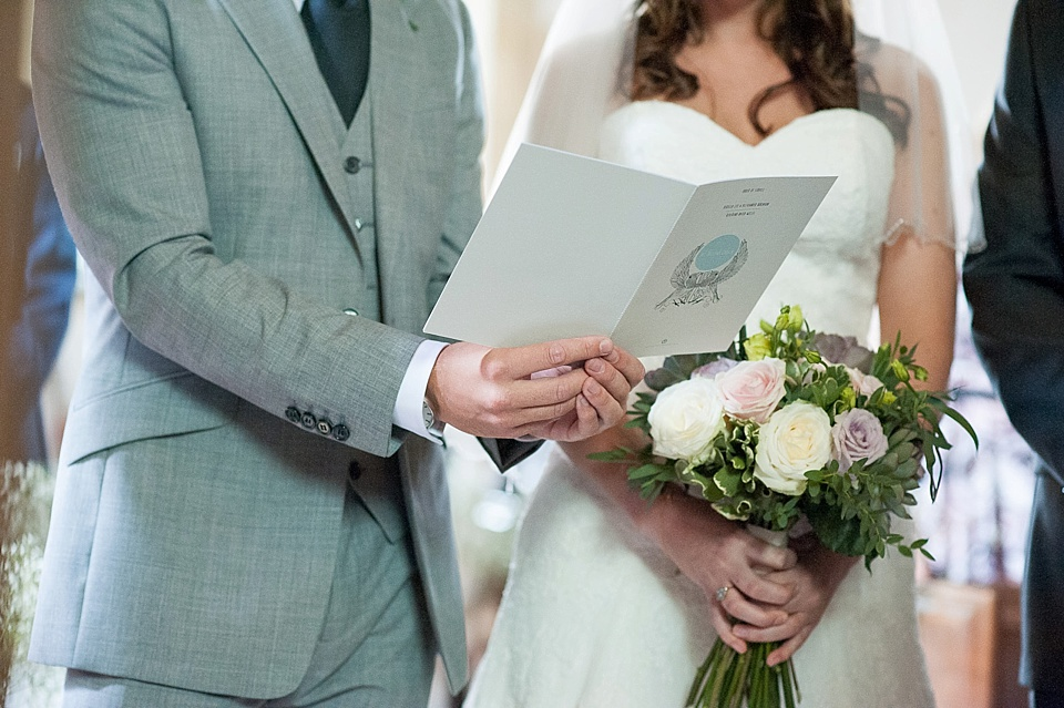 Bride and groom singing from order of service - flowers by Blooms - English country garden wedding All Hallows Church Woolbeding Sussex wedding photographer © Fiona Kelly photography