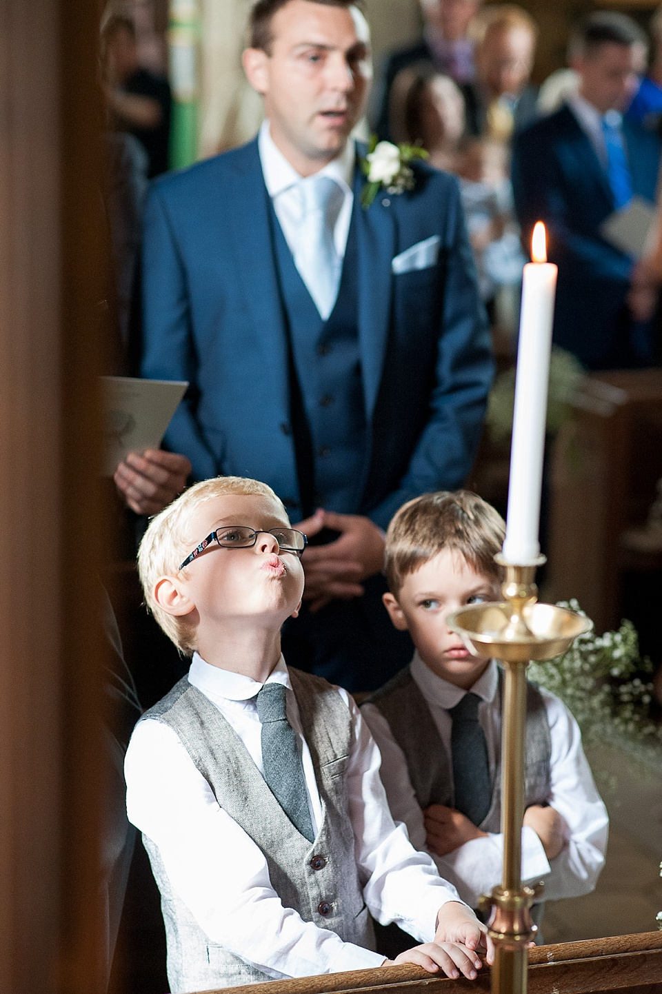 Pageboys looking at candle - English country garden wedding All Hallows Church Woolbeding Sussex wedding photographer © Fiona Kelly photography