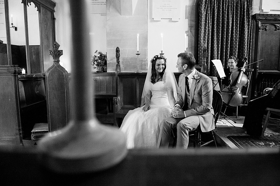 Caught in the moment - bride in lace Lillian West wedding dress sits with groom in church - English country garden wedding All Hallows Church Woolbeding Sussex - natural wedding photographer © Fiona Kelly photography