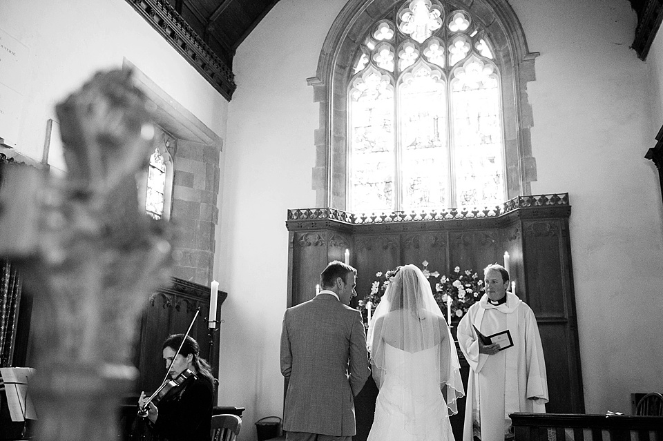 Bride and groom say their vows - English country garden wedding All Hallows Church Woolbeding Sussex - natural wedding photographer © Fiona Kelly photography