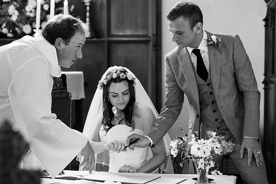 Bride in Lillian West wedding gown with real flower crown signing the register with groom - English country garden wedding All Hallows Church Woolbeding Sussex - natural wedding photographer © Fiona Kelly photography