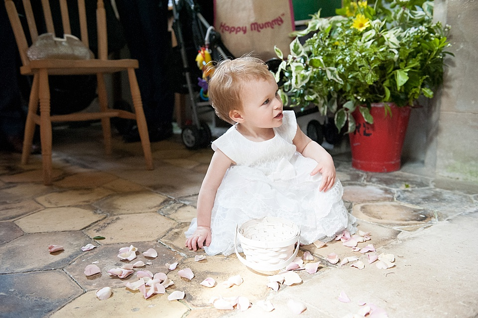 Flower girl playing with petals - English country garden wedding All Hallows Church Woolbeding Sussex - natural wedding photographer © Fiona Kelly photography