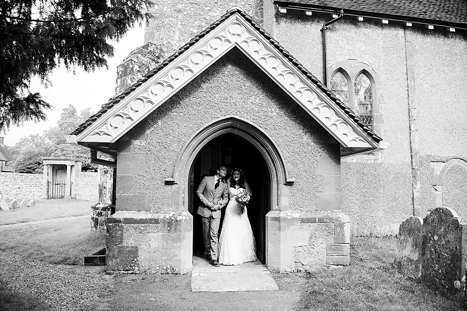 Bride and groom stand in archway of church - English country garden wedding All Hallows Church Woolbeding Sussex - natural wedding photographer © Fiona Kelly photography