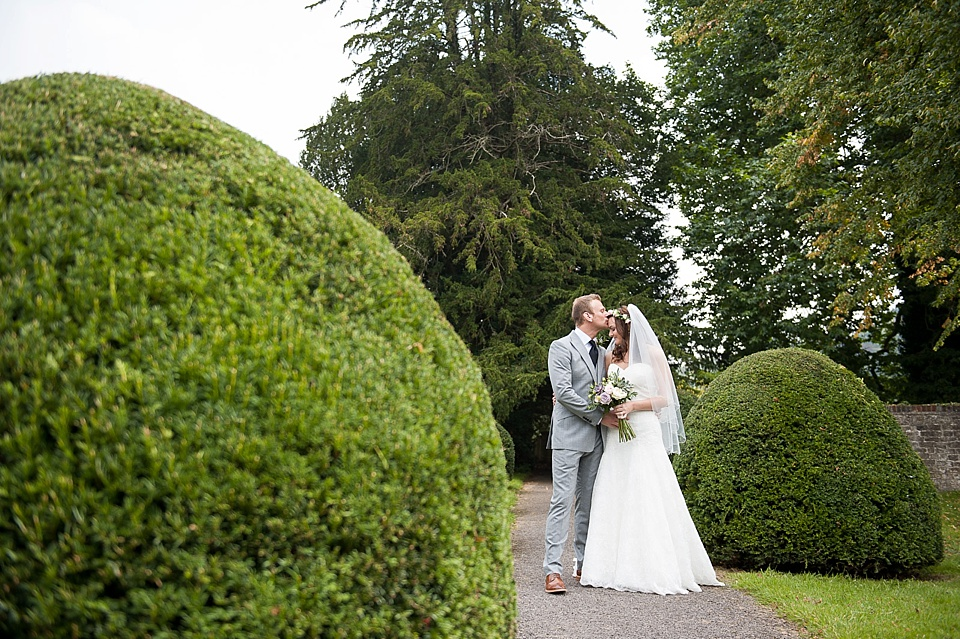 Bride in Lillian West being kissed by groom - English country garden wedding All Hallows Church Woolbeding Sussex - natural wedding photographer © Fiona Kelly photography