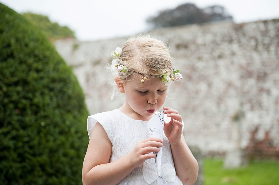 Cute flower girl with confetti cone - English country garden wedding All Hallows Church Woolbeding Sussex - natural wedding photographer © Fiona Kelly photography