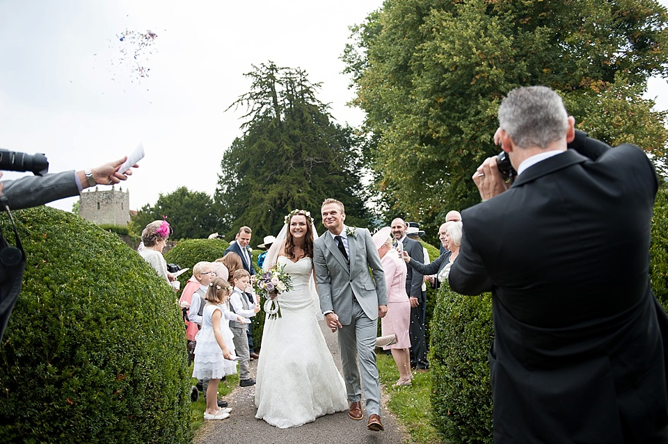 Bride in Lillian West with groom - Confetti time! English country garden wedding All Hallows Church Woolbeding Sussex - natural wedding photographer © Fiona Kelly photography