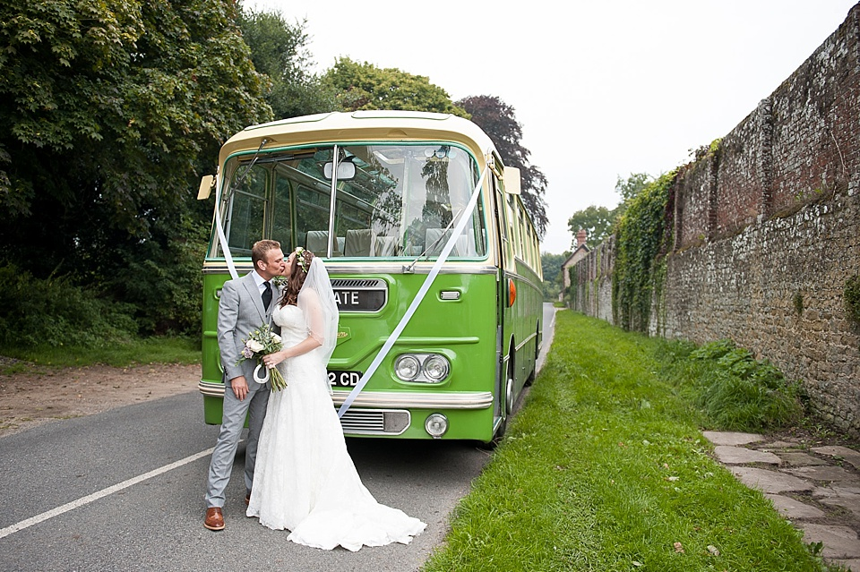 Bride in Lillian West kissing groom next to vintage green bus English country garden wedding All Hallows Church Woolbeding Sussex - natural wedding photographer © Fiona Kelly photography