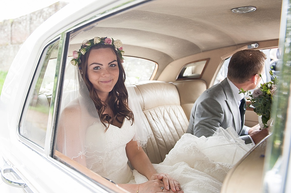 Bride with real flower crown sitting with groom in back of vintage car - English country garden wedding All Hallows Church Woolbeding Sussex - natural wedding photographer © Fiona Kelly photography