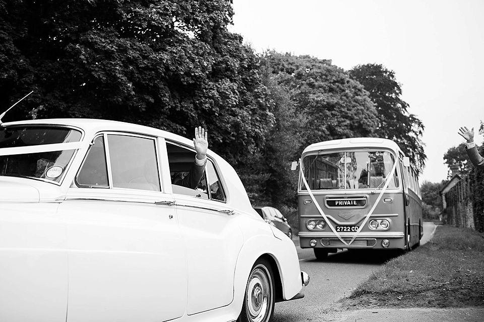 Waving from vintage car with vintage bus - English country garden wedding All Hallows Church Woolbeding Sussex - natural wedding photographer © Fiona Kelly photography