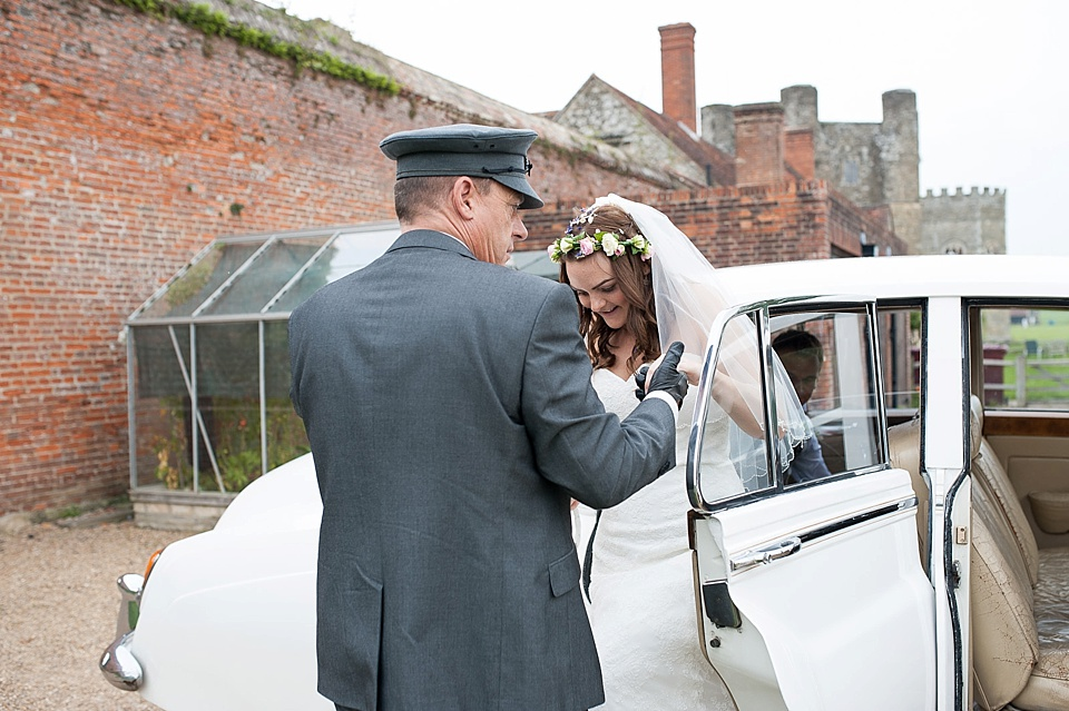 Bride with flower crown and lace dress getting out of vintage car at English country garden wedding at the Walled Garden at Cowdray - Sussex wedding photographer © Fiona Kelly photography