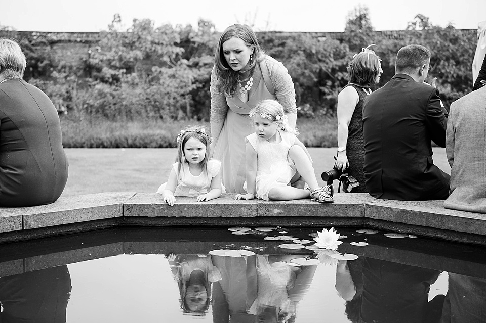 A lady and two children at a pond at the Walled Garden at Cowdray - Sussex at an English country garden - wedding photographer © Fiona Kelly photography