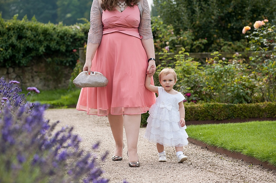 Lady with child wearing white frilly dress at an English country garden wedding at the Walled Garden at Cowdray - Sussex wedding photographer © Fiona Kelly photography