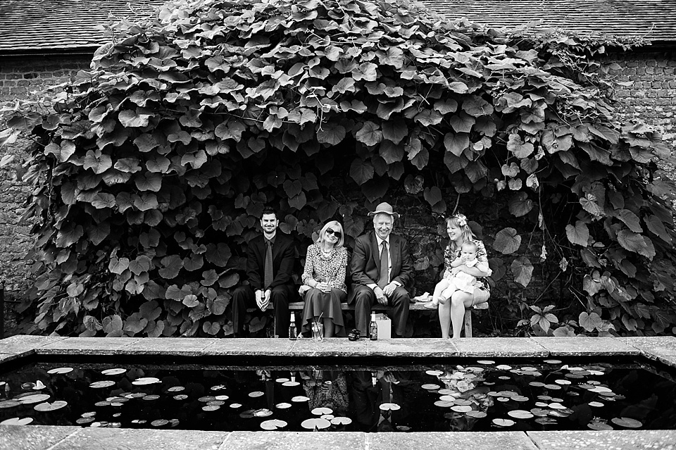 Guests outside by the pond enjoying themselves at an English country garden wedding at the Walled Garden at Cowdray - Sussex wedding photographer © Fiona Kelly photography