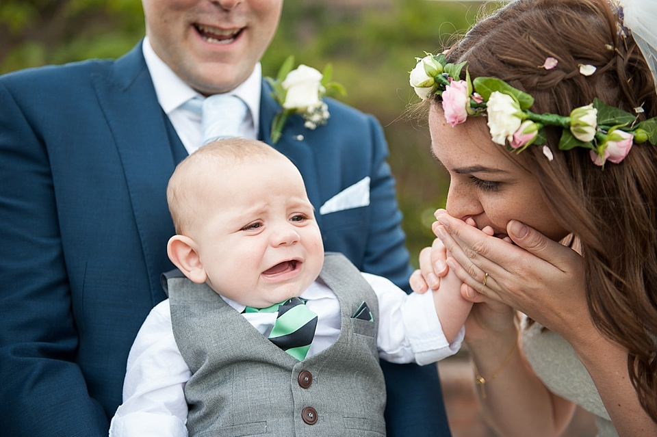 Bride with flowers in hair soothing baby at an English country garden wedding at the Walled Garden at Cowdray - Sussex wedding photographer © Fiona Kelly photography