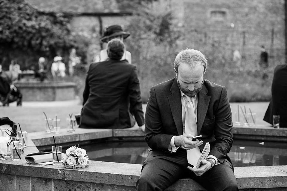 Man texting at a wedding at an English country garden wedding at the Walled Garden at Cowdray - Sussex wedding photographer © Fiona Kelly photography