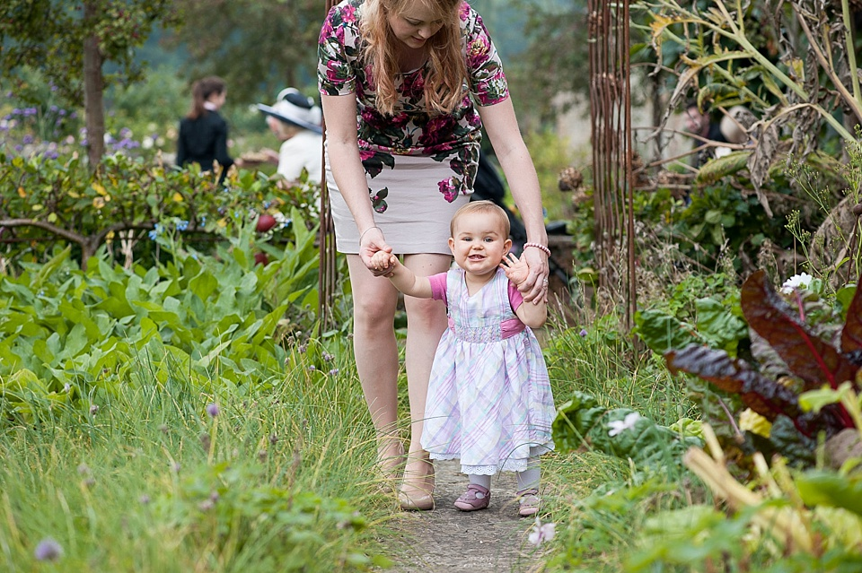 Mum in flower dress with toddler outside an an English country garden wedding at the Walled Garden at Cowdray - Sussex wedding photographer © Fiona Kelly photography