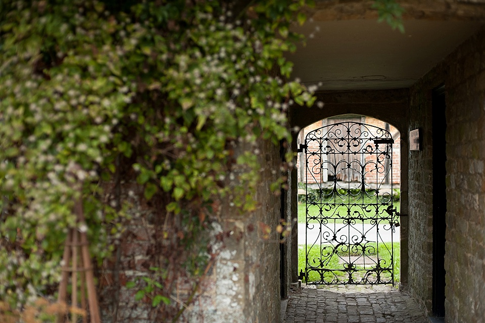 Beautiful arch doorway with a delicate gate at an English country garden wedding at the Walled Garden at Cowdray - Sussex wedding photographer © Fiona Kelly photography