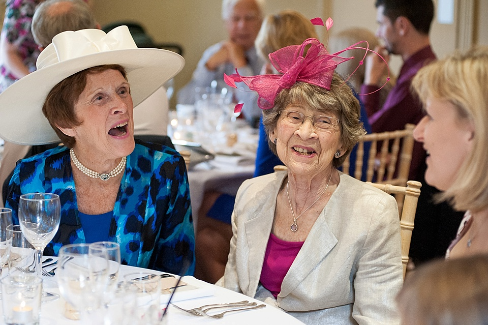 Two ladies wearing fancy hats at an English country garden wedding at the Walled Garden at Cowdray Sussex - natural wedding photographer © Fiona Kelly photography