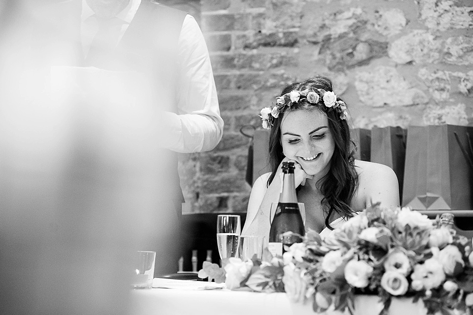 Beautiful bride with flowers in hair smiling as Father delivers speech at an English country garden wedding at the Walled Garden at Cowdray Sussex - natural wedding photographer © Fiona Kelly photography