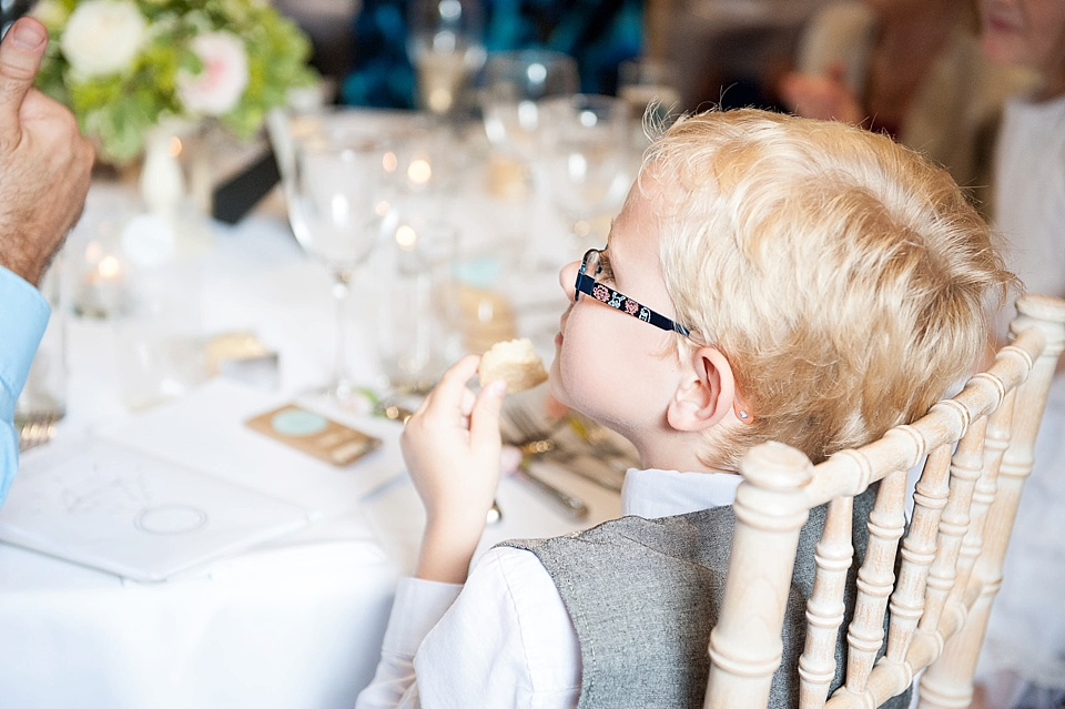 Pageboy eating bread at English country garden wedding at the Walled Garden at Cowdray Sussex - natural wedding photographer © Fiona Kelly photography