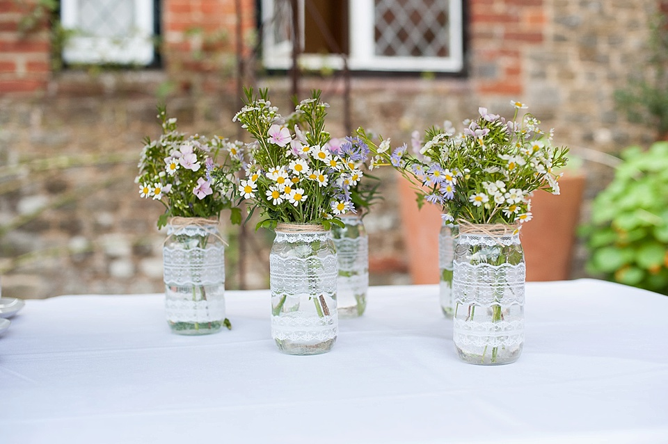 Daisies in mason jars wrapped in lace by Blooms florist - English country garden wedding at the Walled Garden at Cowdray Sussex - natural wedding photographer © Fiona Kelly photography