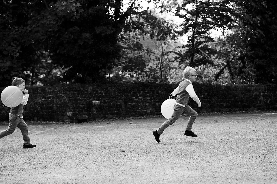 Page boys playing with balloons in black and white at English country garden wedding at the Walled Garden at Cowdray Sussex - natural wedding photographer © Fiona Kelly photography
