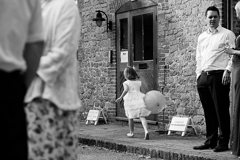 Flower girl playing with balloon - English country garden wedding at the Walled Garden at Cowdray Sussex - natural wedding photographer © Fiona Kelly photography