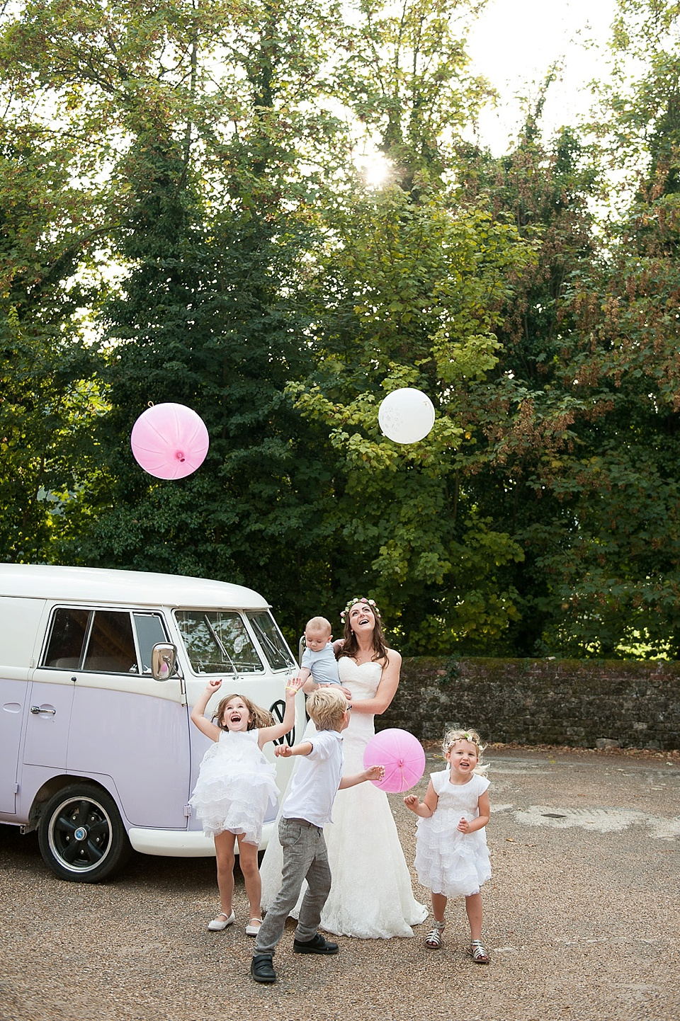 Page boys flower girls and bride by vintage VW camper van releasing giant balloons - English country garden wedding at the Walled Garden at Cowdray Sussex - natural wedding photographer © Fiona Kelly photography