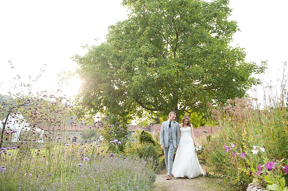 Just married walking through the gardens at English country garden wedding at the Walled Garden at Cowdray Sussex - natural wedding photographer © Fiona Kelly photography