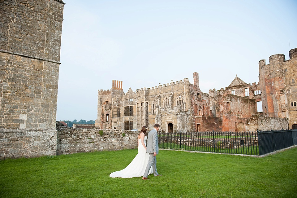 Bride and groom walking in front of dramatic venue - English country garden wedding at the Walled Garden at Cowdray - Sussex wedding photographer © Fiona Kelly photography